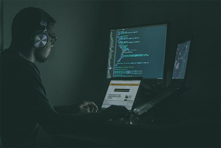 Mann, der einen Computerbildschirm mit Code betrachtet